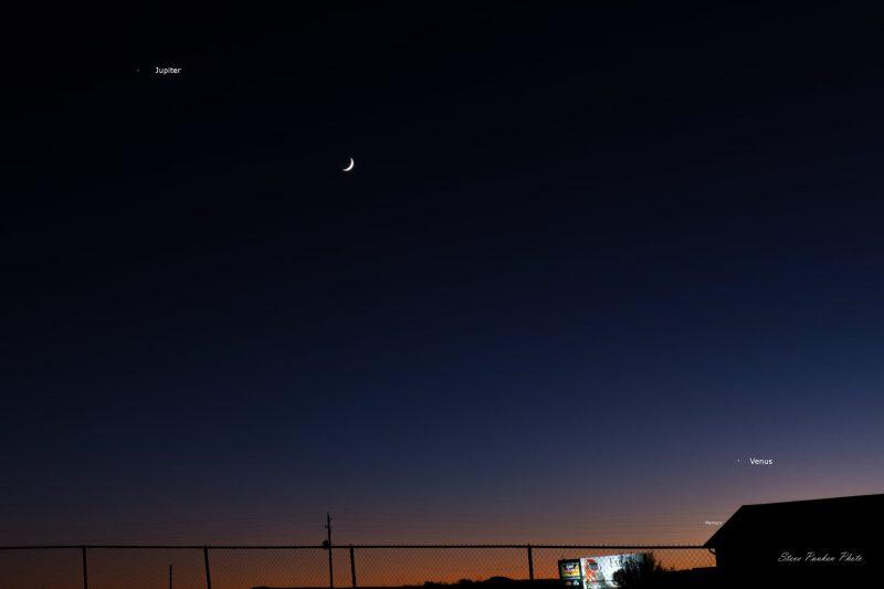 Thin crescent young moon between Venus and Jupiter at dusk.
