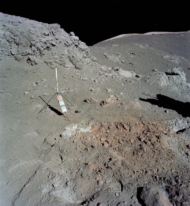 Hilly lunar landscape, mostly gray with orange soil with spacesuit footprints in it.