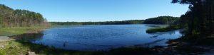 Circular blue pond under a cloudless sky.
