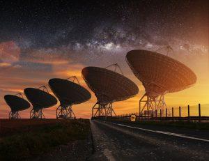 Row of radio telescopes with starry night sky.