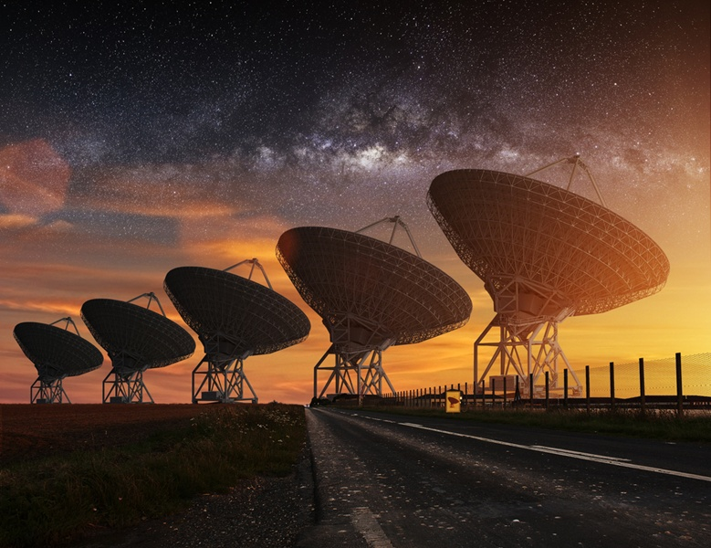Row of five giant radio telescopes with Milky Way stretching above them.