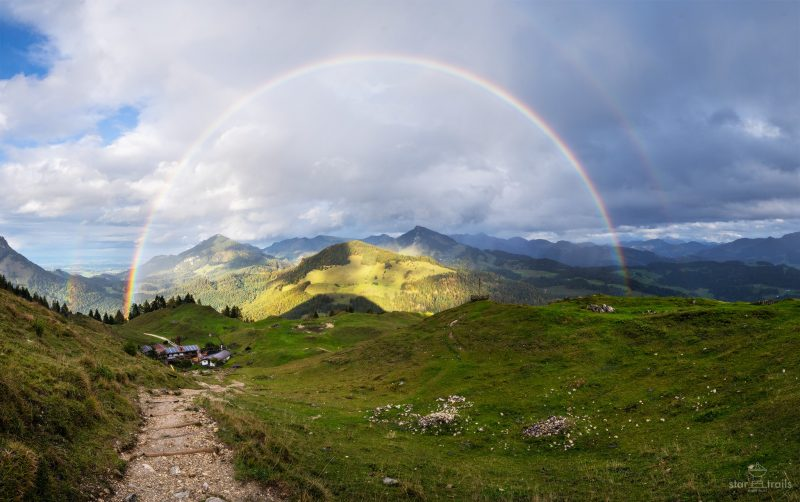 Rugged mountains behind perfect semicircular double rainbow.