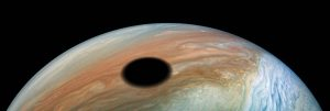 A large, round, black shadow on Jupiter's clouds.