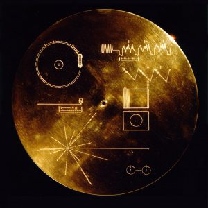 A gold-colored record with human symbols etched on its surface.