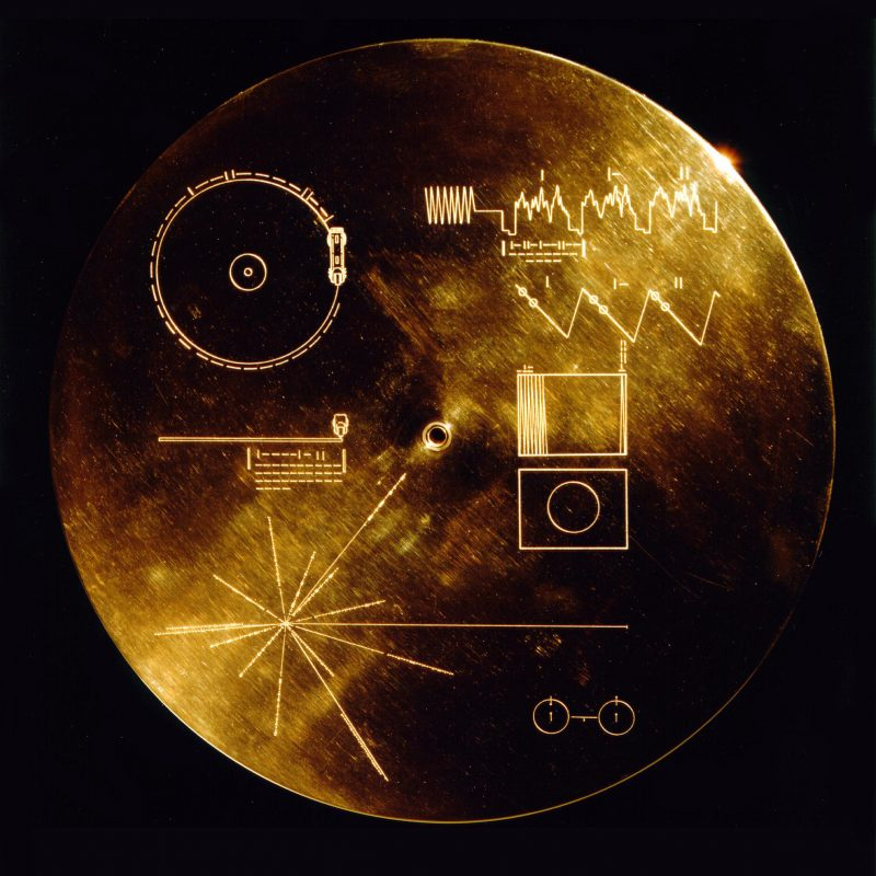A gold-colored disk-shaped record with human symbols etched on its surface.