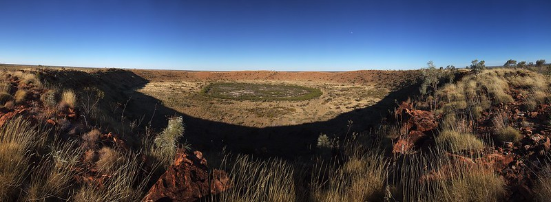 Panorama view of whole crater showing greenish patch of brush in middle.