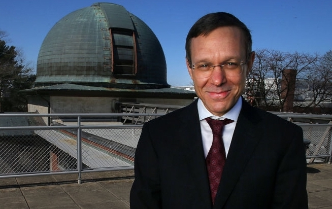 Man smiling with observatory in background.