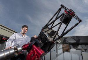 Smiling man standing next to telescope.