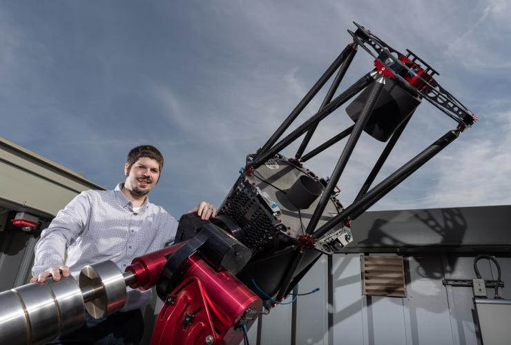 Smiling man standing next to large open-frame reflector telescope.