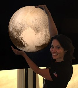 """Woman """"holding"""" a photo of Pluto."""