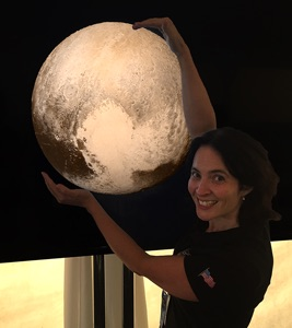 Young woman appearing to hold up an image of Pluto.