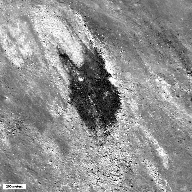 Blotch of dark material on top of lighter rocky surface.