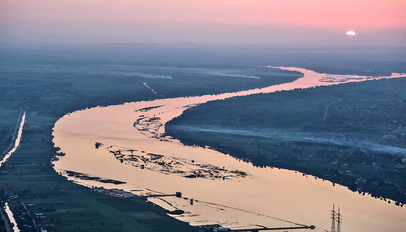 Wide river shining in the sunset, winding into the distance.