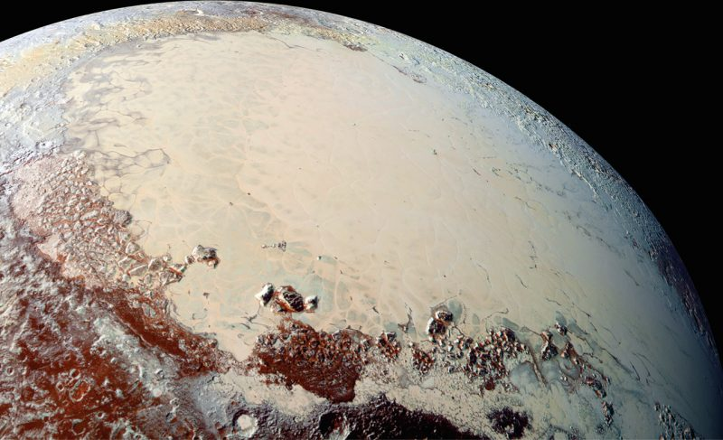 Smooth white icy plains on a small planet viewed from orbit, also dark red patches.