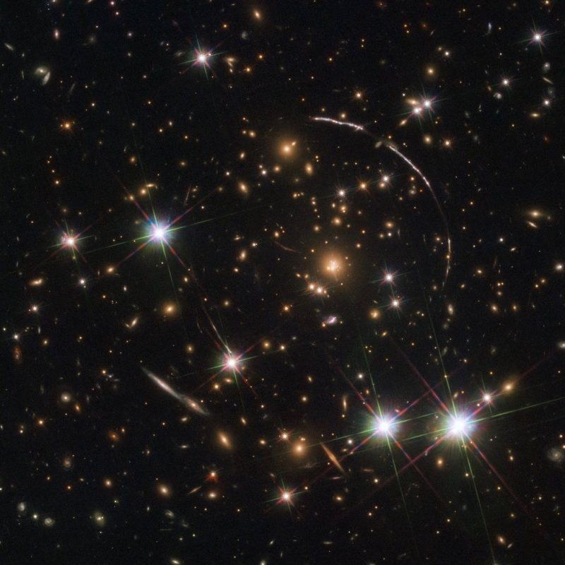 Star field with stars, very distant galaxies, and broken circle of curved arcs.