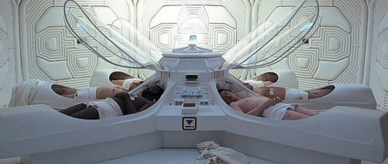 Scene from a movie, with nearly nude astronauts lying in coffin-like hibernation capsules.