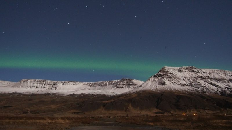 Thin green aurora over rocky snow-covered mountains.