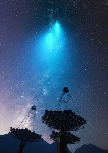 A dish-type telescope, at night, beneath a cascade of bright radiation.