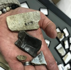 A hand showing pieces of flat rock.