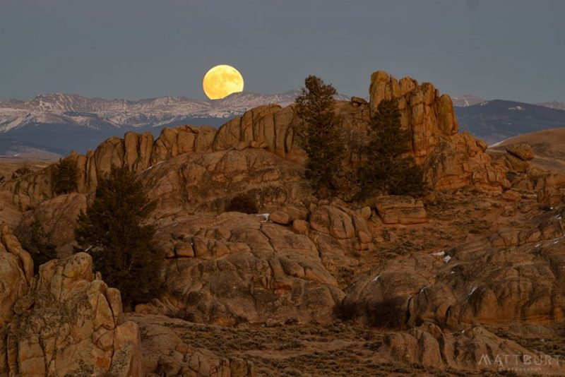 Full moon behind distant mountains. Large brown vertical outcrops in foreground.