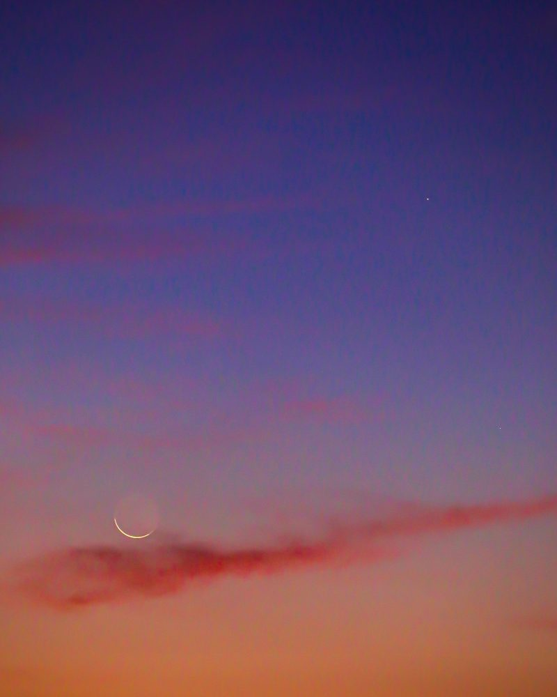 Very thin crescent moon near a bright planet, in a brightly lit twilight sky.