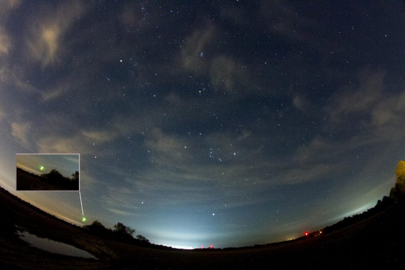 Panorama of sky with constellation Orion prominent and one bright meteor.