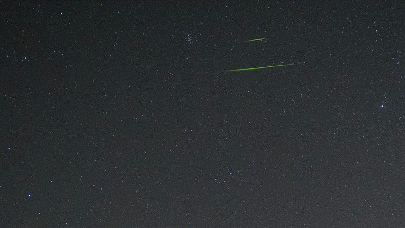 Two thin green horizontal streaks in starry sky.