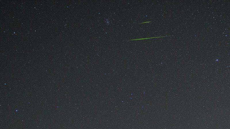 Two thin green horizontal streaks in starry sky.