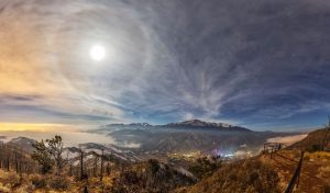The moon with a halo around it over a mountain landscape