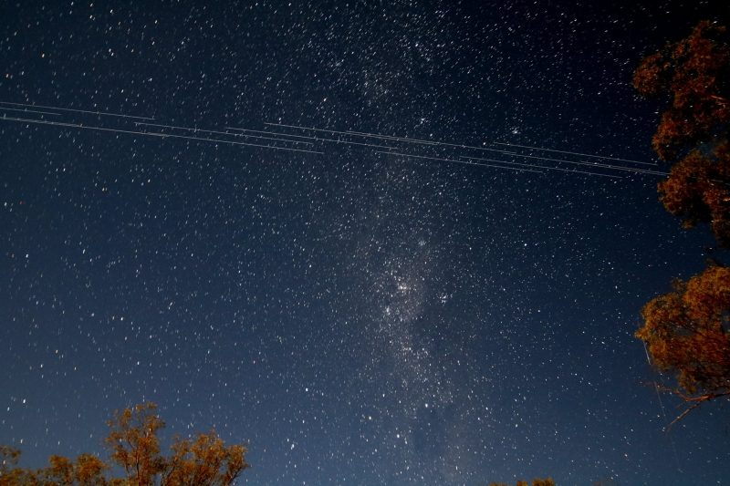Dark, starry night sky with several thin lines of satellites crossing the sky.