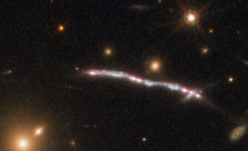 Star field with slightly fuzzy nodular-looking curved white streak across it.