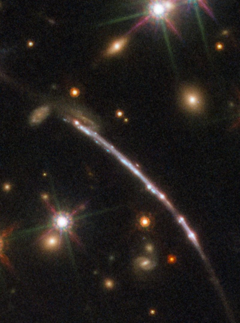 Several small, fuzzy galaxies inside a big white nodular curved streak of light.