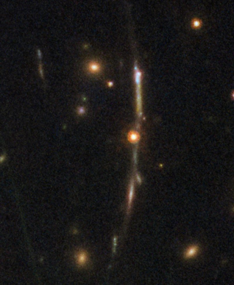 Slightly curved vertical arc of light with stars and faint tiny galaxy.