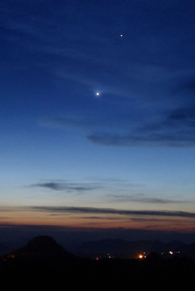 Two very bright planets in a twilight sky over a dark, hilly horizon.