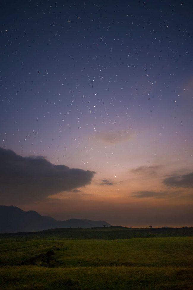 Venus and Jupiter over a hilly rural landscape, in a twilight sky.