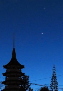 Venus and Jupiter over a domed and peaked roofline (like a temple).