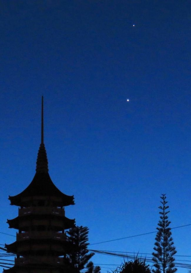 Venus and Jupiter over a domed and peaked roofline (like a pagoda).