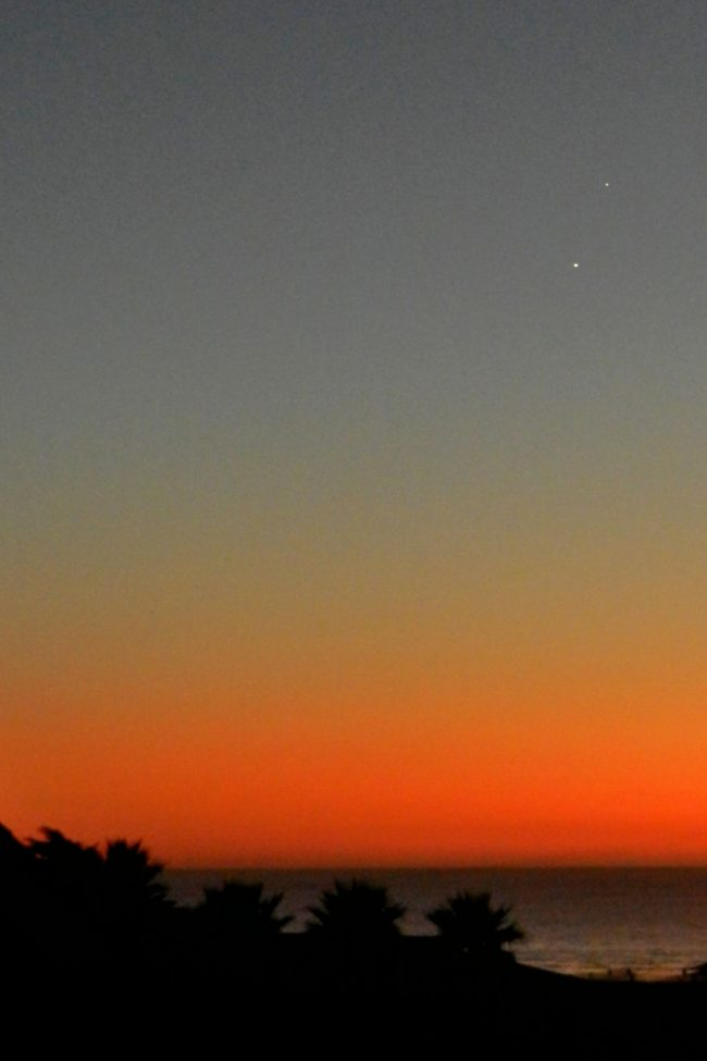 Venus and Jupiter in bright blue to orange twilight, above the ocean.
