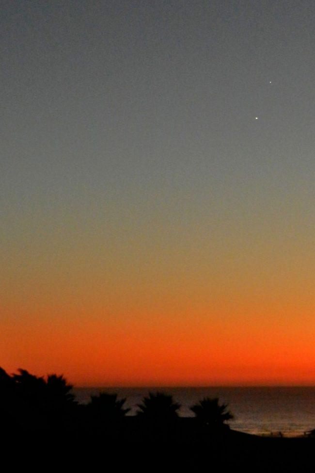 Venus and Jupiter in bright blue to orange twilight, above the ocean.
