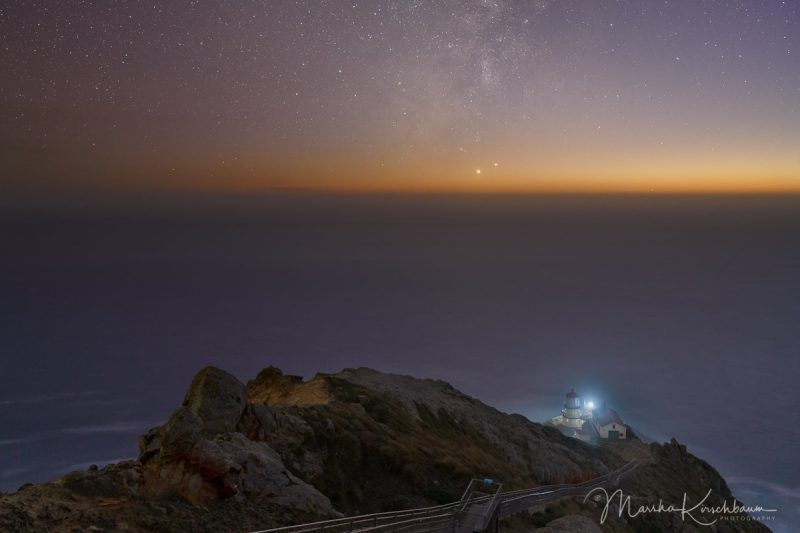 Venus and Jupiter over misty, twilit ocean horizon, with a lighthouse in the foreground.