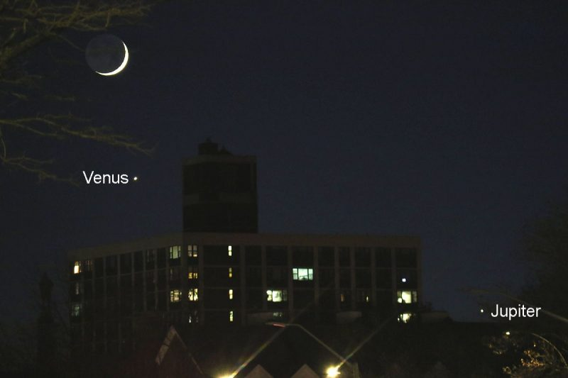 Moon, Venus, Jupiter setting behind buildings.