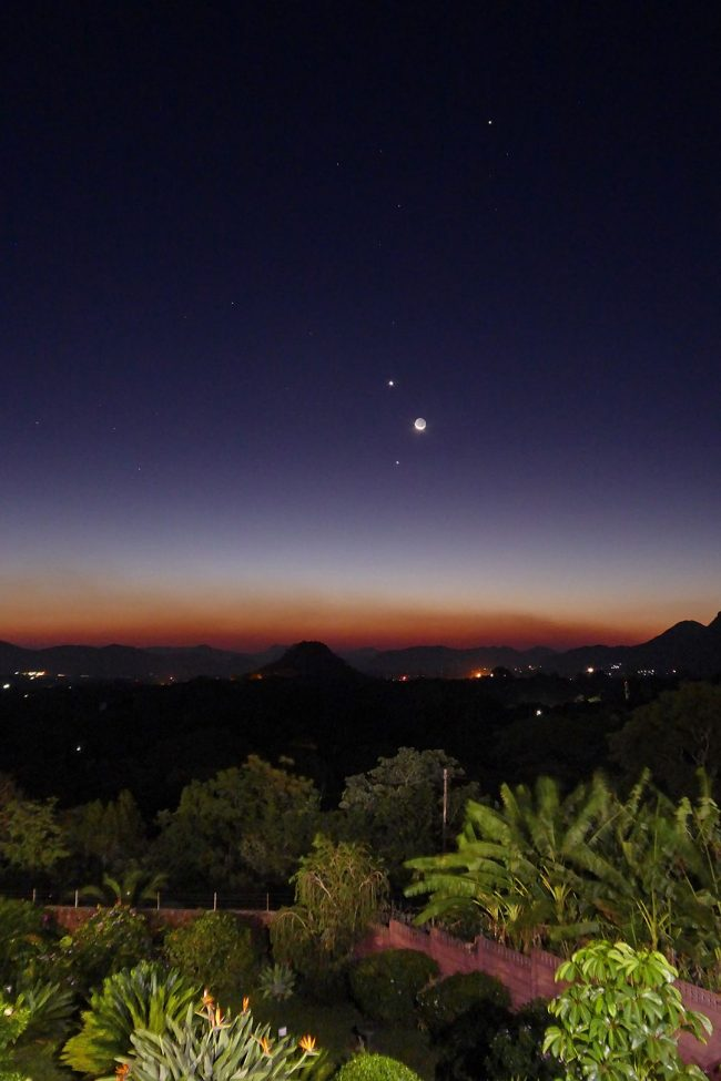Planets and moon in twilight above brushy landscape with conical hills in distance.