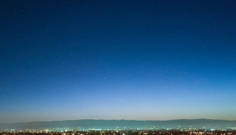Venus, Jupiter and Saturn in a twilight sky over long, low hills in the distance.