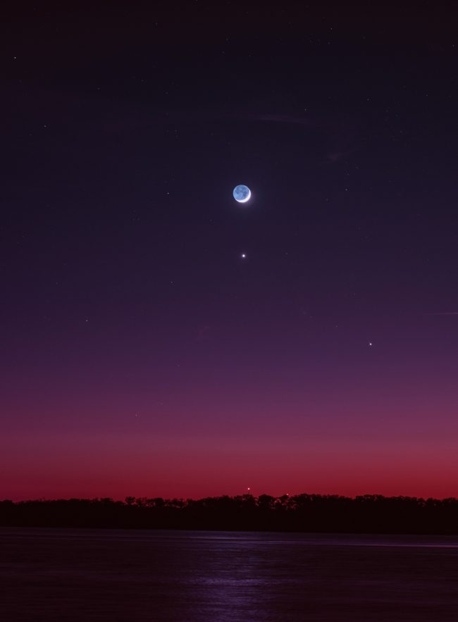 Moon, with earthshine, and Venus in blue twilight fading to red on horizon.