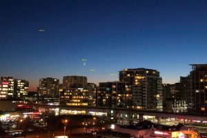 Planets and moon over a small city skyline.