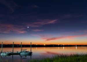 Beautiful twilight sky above a marina, with Venus directly below the crescent moon.