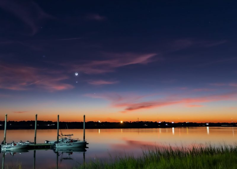Beautiful twilight sky above a marina, sailboats in foreground, with Venus directly below the crescent moon.
