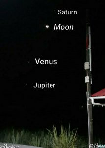 Worlds extending above the horizon in a line: from bottom, they are Jupiter, Venus, the moon, Saturn.