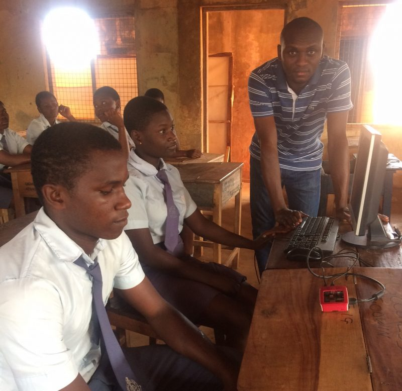 Young men looking at a small red box on a table in a classroom.