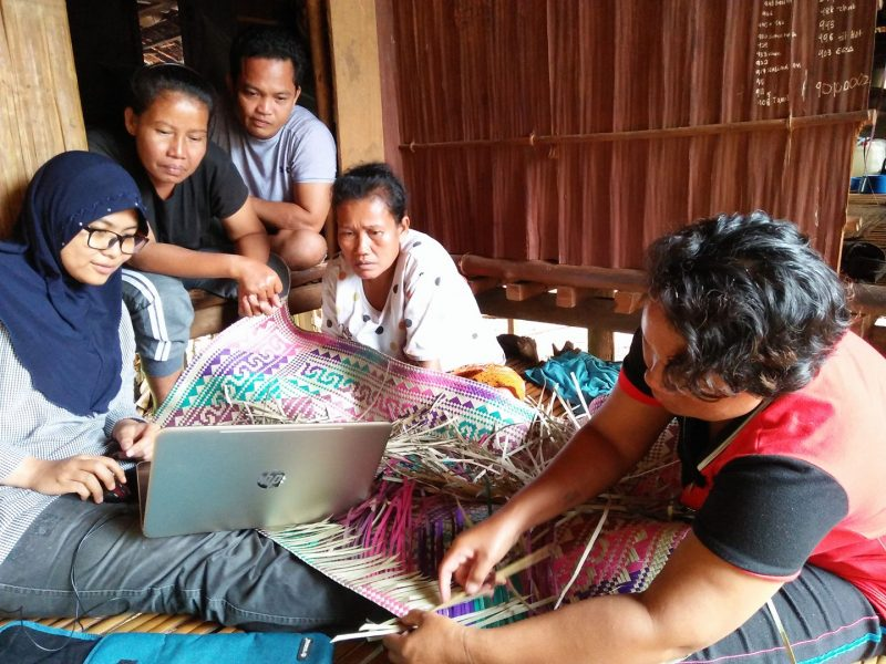People gathering around a laptop sitting on a colorful half-finished woven rug.